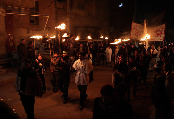 The Iraqi procession on the streets outside Seyyida Zainab. People are carrying Mishaals. Photo by Ketan Gajria