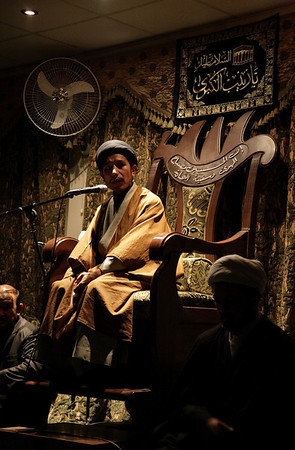 The Afghan Sayyid with the black turban is sitting on the minbar reading the majlis on the night of the 9th of Moharram. Photo by Ketan Gajria